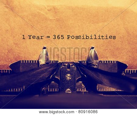 old typewriter with paper and a quote: 1 year = 365 possibilities toned with a retro vintage instagram filter effect app or action