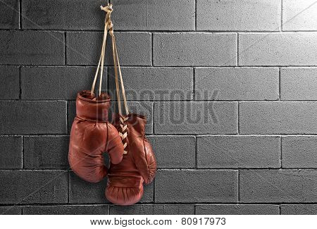 Pair Of Vintage Boxing Gloves Hanging On A Wall
