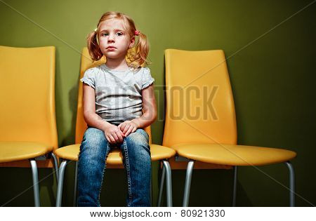Little Redhead Girl Waiting In Reception Room.