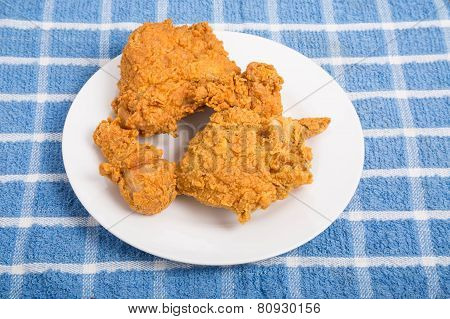 Fried Chicken On White Plate On Blue Plaid Towel