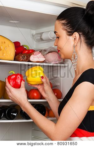 beautiful woman chooses peppers from the fridge