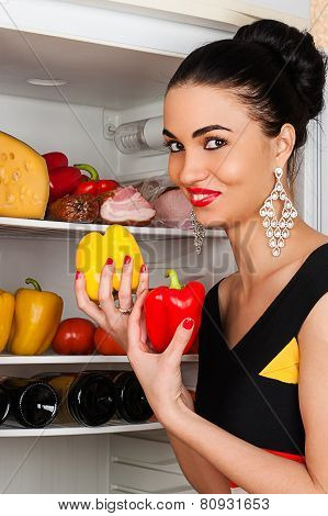 beautiful woman takes peppers from the fridge smiling
