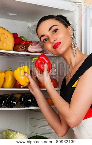 beautiful woman takes peppers from the fridge