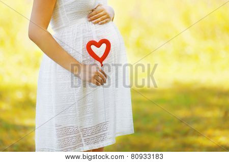 Pregnancy, Maternity And New Family Concept - Pregnant Woman And Heart Symbol Outdoors In Sunny Summ