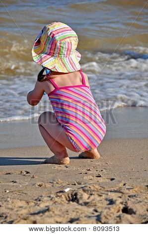 little girl sitting at the shore and observing waves
