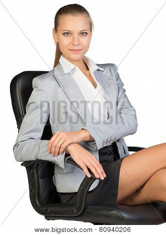 Businesswoman on office chair, looking at camera
