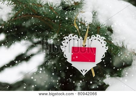 White Valentines lace heart with card on the snow fir tree