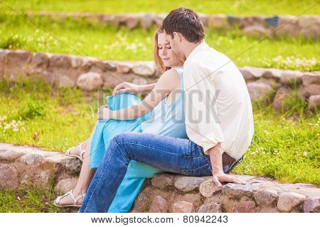 Portrait Of Young Caucasian Couple Showing Their Intimacy And Sensuality While Sitting Outdors Toget