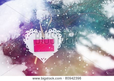 Snowy background with white Valentines lace heart with card