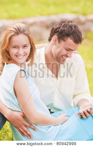 Happy Caucasian Couple Sitting Together Outdoors While Using Pda Handheld
