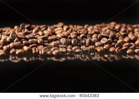 Line Of Aromatic Roasted Coffee Beans Placed Over Black Background.