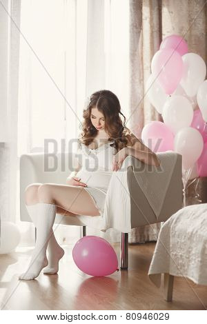 Pregnant woman in a white nightgown with balloons.