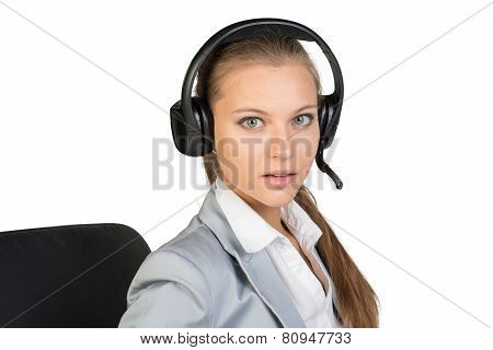 Businesswoman in headset sitting on chair