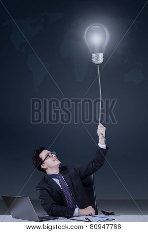 Young Caucasian Manager Pulling Lightbulb