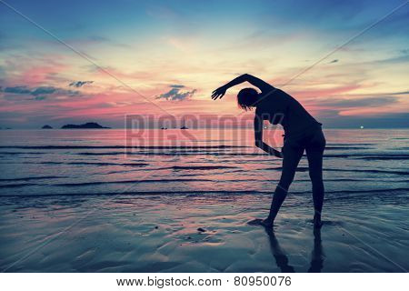 Female silhouette doing exercises on the ocean beach at sunset time.