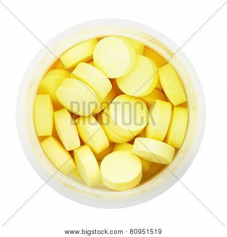 Top View Of Yellow Pills In Round Plastic Bottle