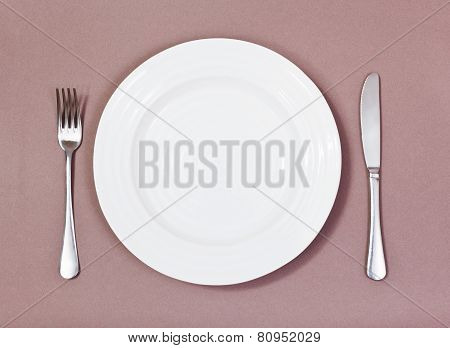 Top View Of White Plate, Fork, Knife On Brown