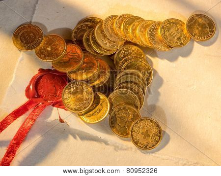 Twenty Swiss Francs gold coins with feather and old parchment