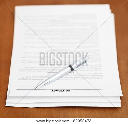 Sheets Of Contract And Silver Pen On Wooden Table