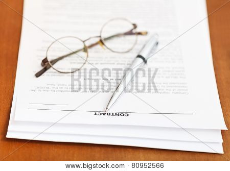 Contract And Silver Pen And Eyeglasses On Table