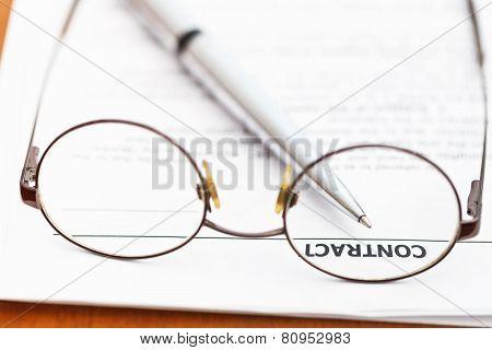 Contract And Silver Pen Through Eyeglasses