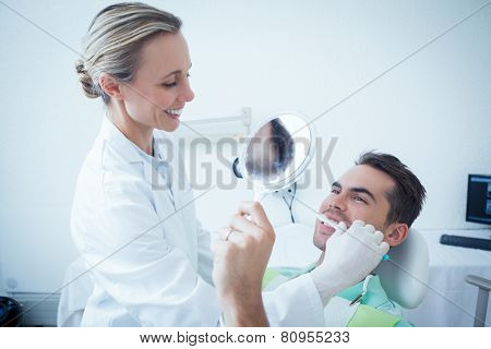Female dentist brushing mans teeth in the dentists chair