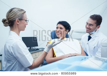 Male dentist and assistant with female patient in the dentists chair