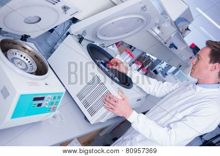 Chemist in lab coat using a centrifuge in laboratory