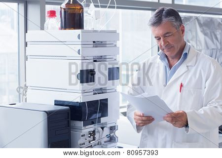 Scientist standing in lab coat reading analysis in laboratory