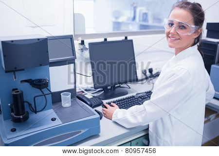 Portrait of a smiling young scientist with safety glasses in laboratory
