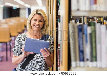 Mature student studying in the library with tablet at the university