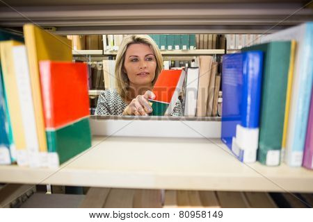 Mature student taking a book in library at the university