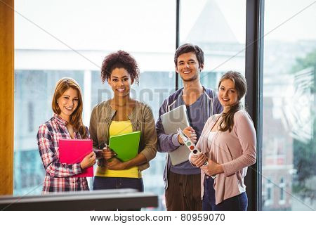 Four smiling classmates standing in front of the window in library