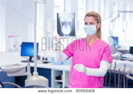 Dentist in surgical mask looking an x-ray at the dental clinic
