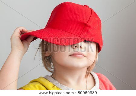 Studio Portrait Of Funny Baby Girl In Red Baseball Cap