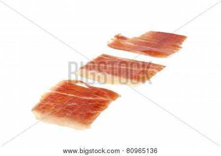 Three spanish serrano ham slices isolated on white background.