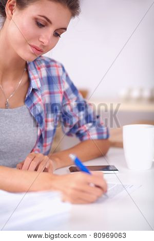 Young woman writing something in her note pad
