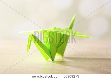 Origami crane on wooden table, on light background