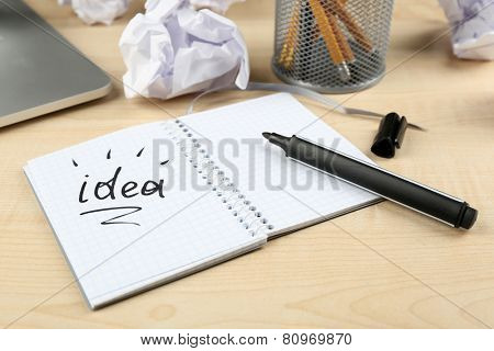 Working mess with crumpled paper, inscription Idea and notebook on wooden table background