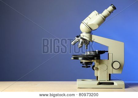 Microscope on table, on color background