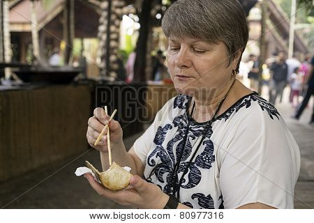 Woman eating Chinese chopsticks rice cooked in bamboo