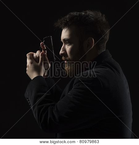 Serious Young Man Holding Gun Facing Left