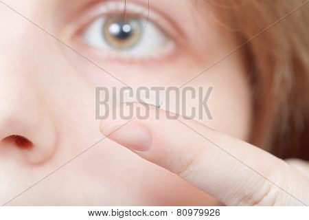 Finger With Contact Lens Near Woman's Face