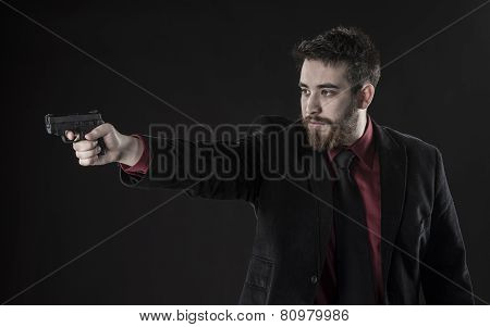 Young Man in Black Suit Aiming a Gun