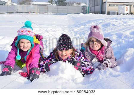 Three girls playing in the snow