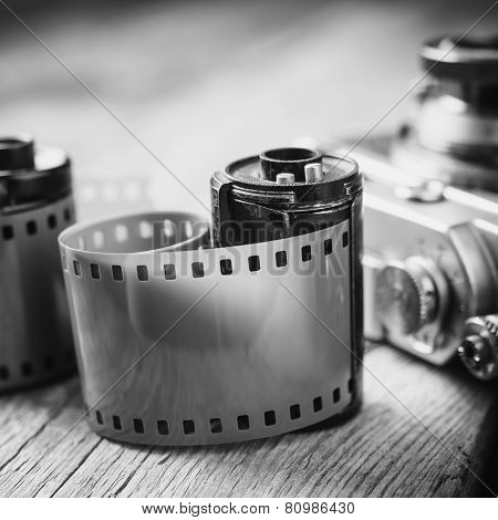 Old Photo Film Cassette And Retro Camera On Background. Vintage Black And White Stylized.