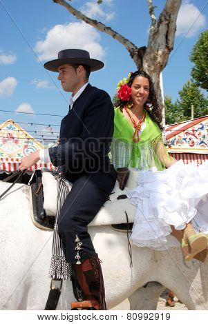 Spanish couple on a horse.