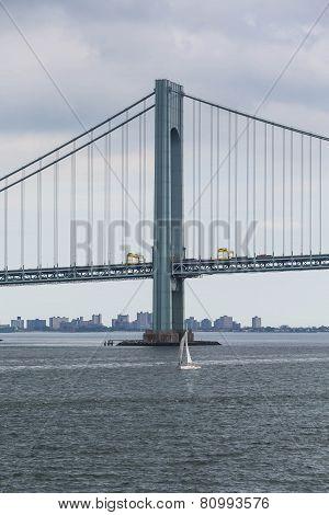 White Sailboat Under Suspension Bridge