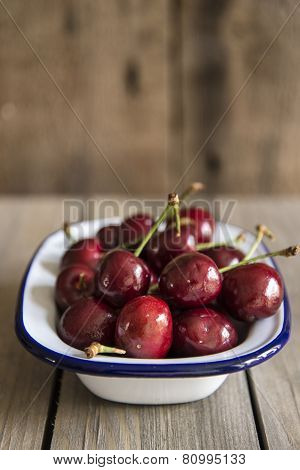 Cherries In Rustic Kitchen Setting With Wooden Background