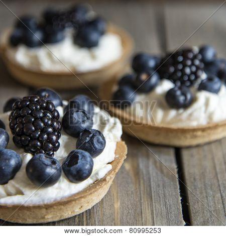 Fresh Fruit Tartlets On Rustic Wooden Kitchen Background